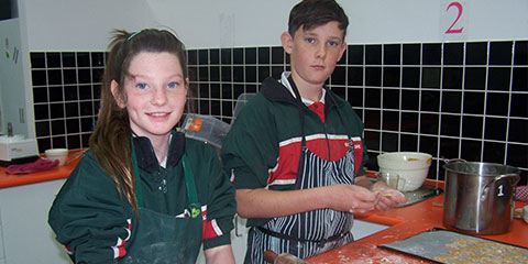 two students cooking in the kitchen at school